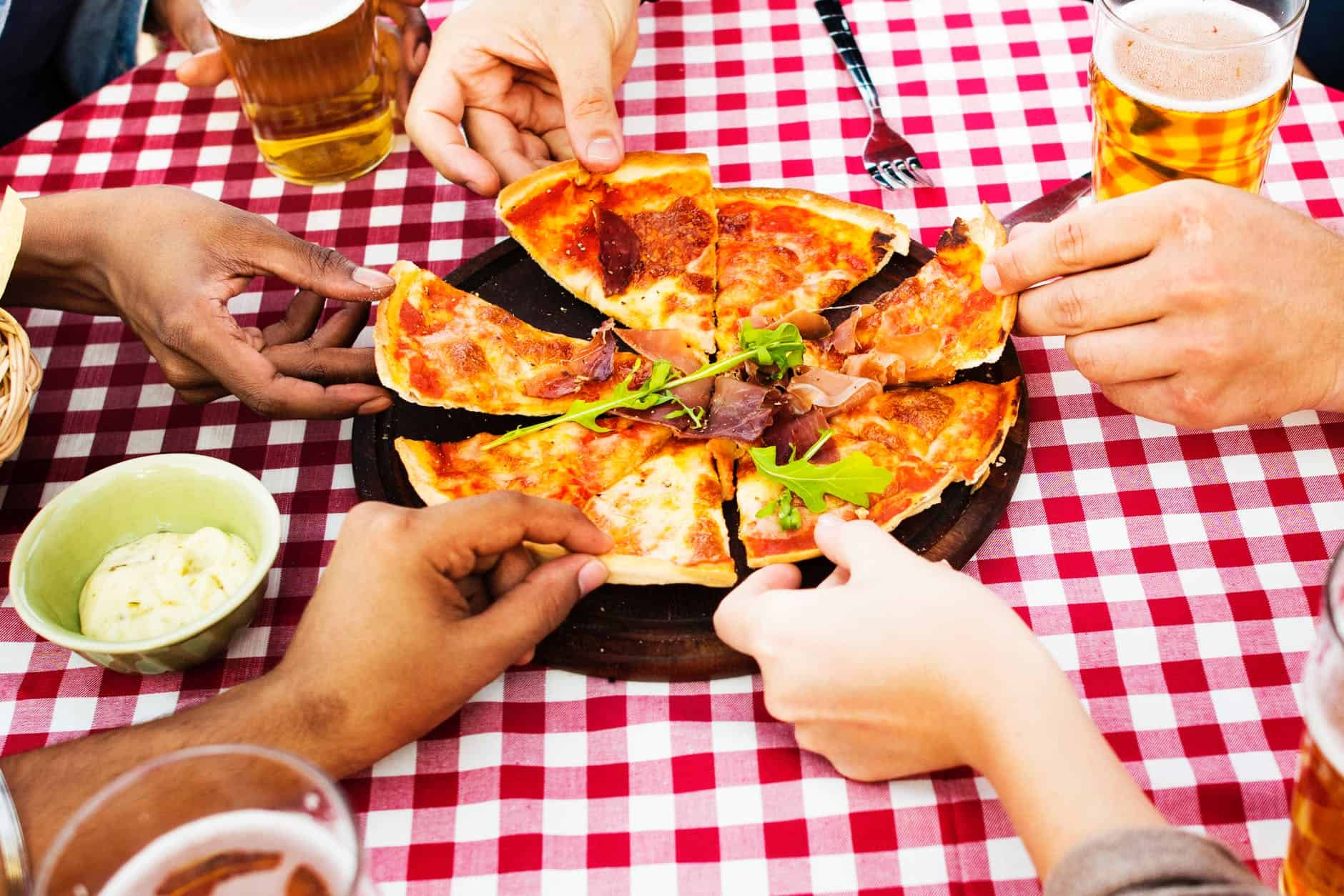 image contains a pizza being shared