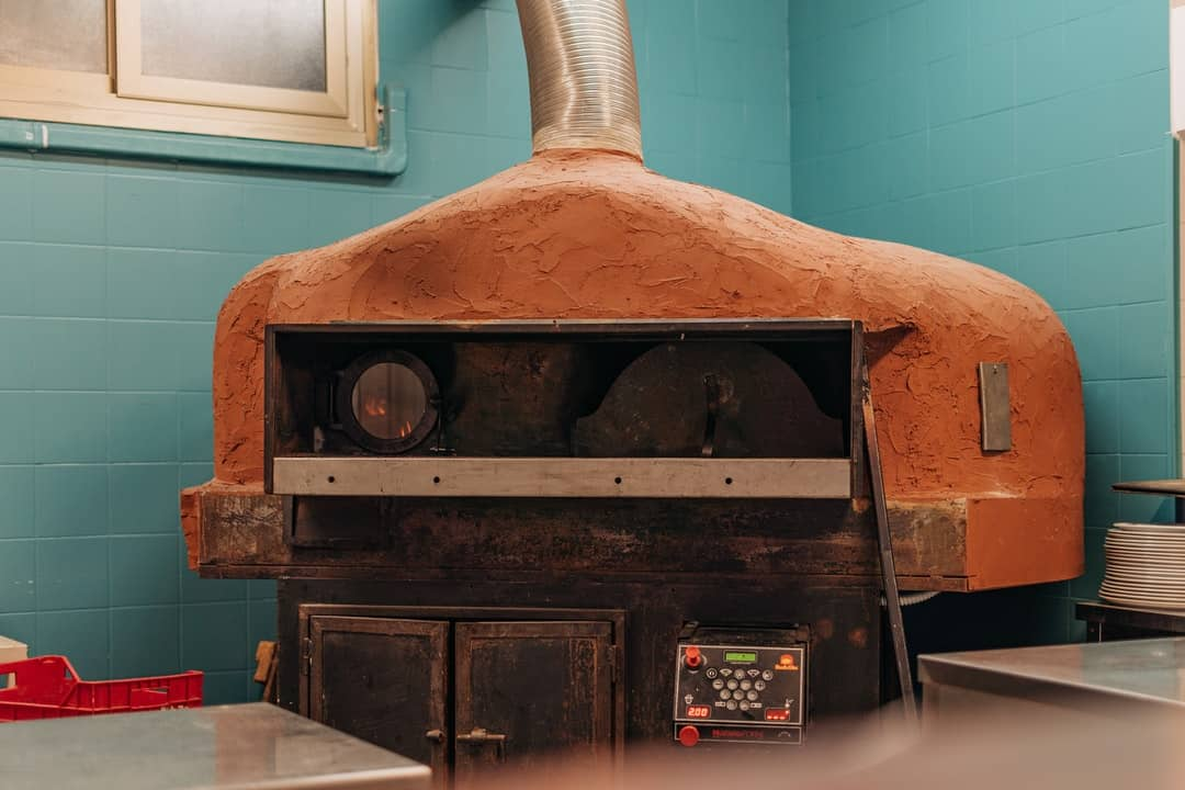 A stove top oven sitting next to a window