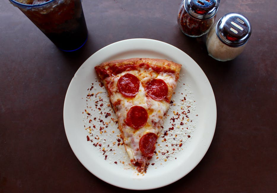 A pizza sitting on top of a plate of food on a table