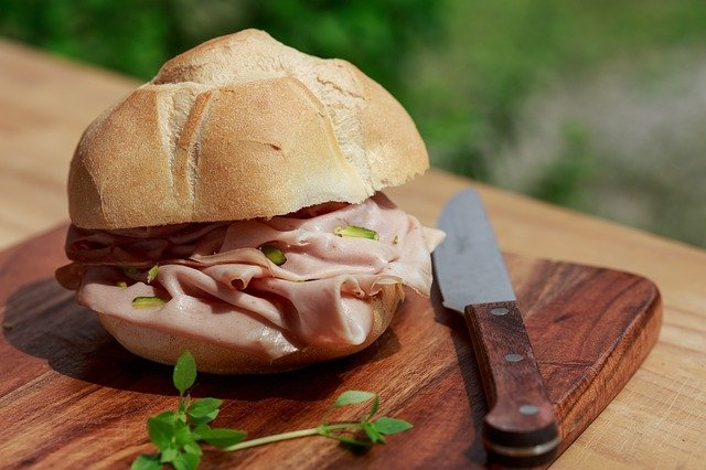 A close up of a sandwich sitting on top of a wooden cutting board